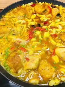 Spanish Paella Provence ingredients sprinkled with spices and covered with stock